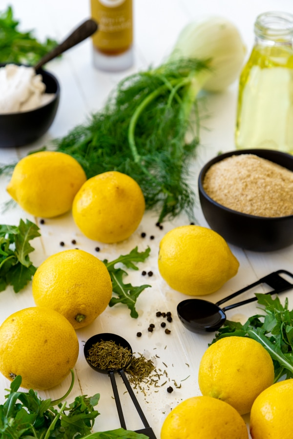 Ingredients for arugula and fennel salad with fried lemons including lemons, fennel, and spices in black measuring cups and spoons on a white board.