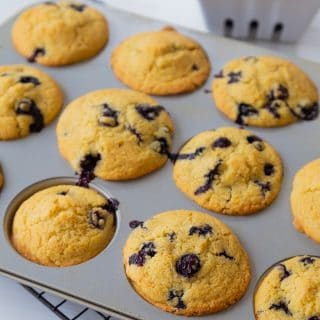 Blueberry muffins in a muffin tin with a white ceramic dish of blueberries in the background.