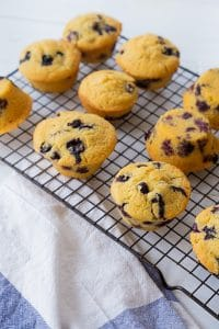 Blueberry muffins cooling on a wire rack with a white and blue towel next to them.