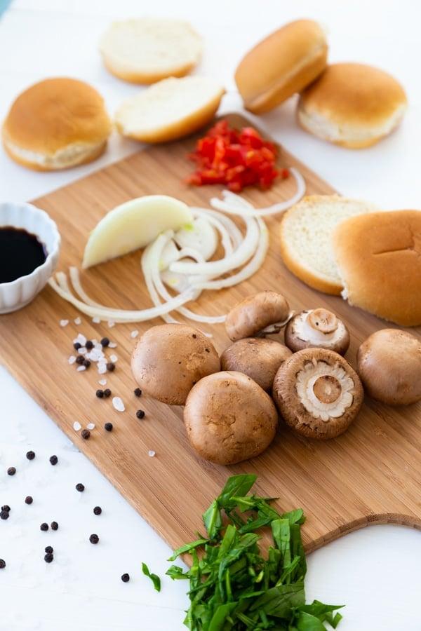 A cutting board with mushrooms, onion, and hamburger buns