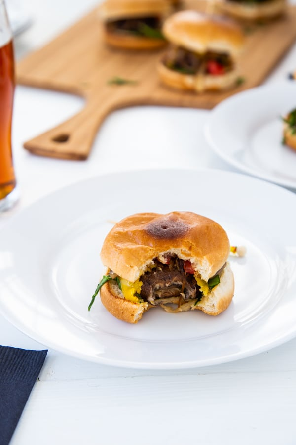A mushroom slider with a bite taken out of the center on a white plate