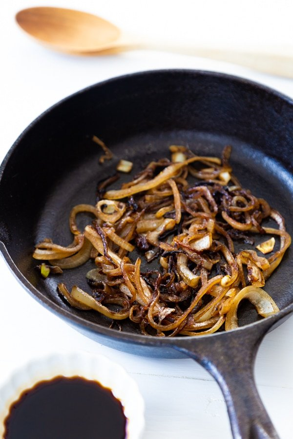 Fried onions in an iron skillet with a white dish of soy sauce and a wood spoon next to it.