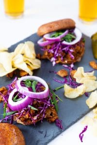Two BBQ sandwiches from the Veganosity cookbook Great Vegan BBQ without a Grill with potato chips and two glasses of beer.