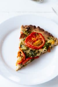 A slice of tomato tart on a white plate made by Veganosity