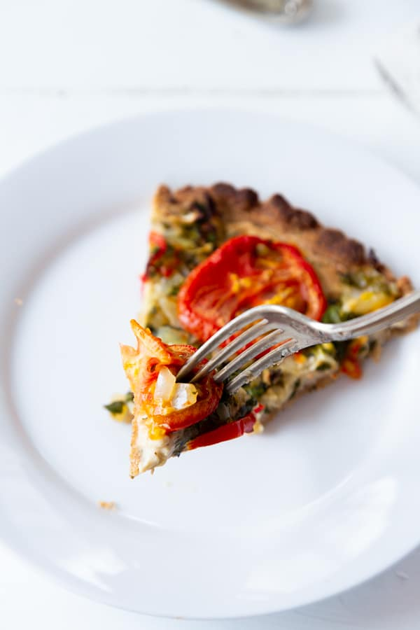 A slice of tomato tart on a white plate with a silver fork cutting into it.