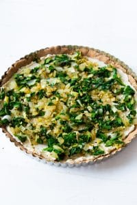 Onion and spinach spread over a tart in a tart pan
