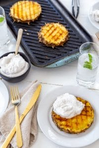 A grill pan with grilled pineapple and a white plate with a slice of grilled pineapple and whipped cream and a black bowl with cream and gold utensils.