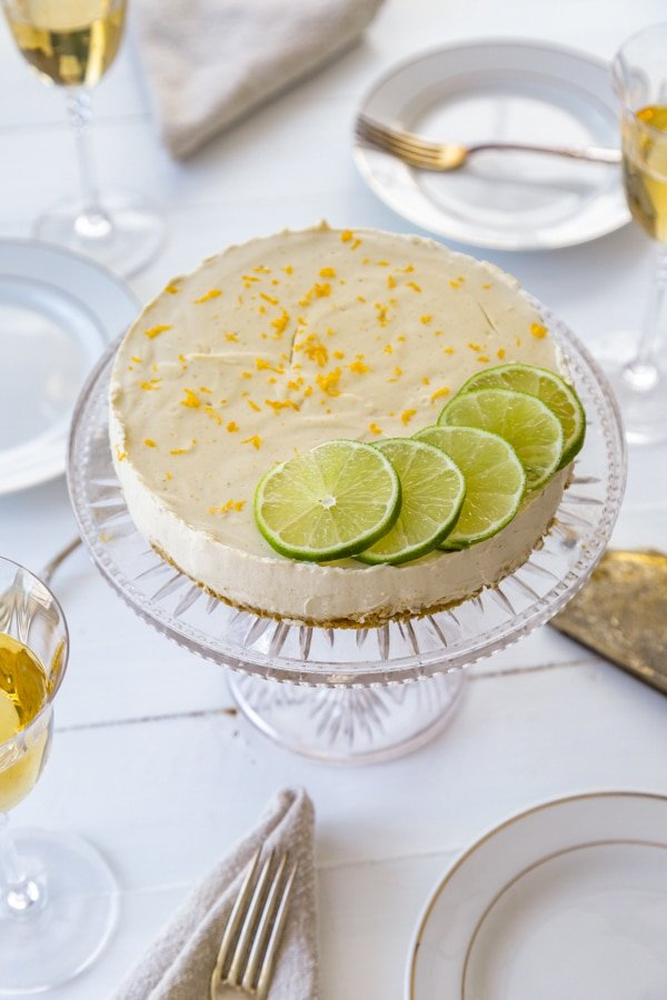 A cheesecake on a glass cake plate with lime slices and lime and orange zest on a white table with plates and glasses of wine next to it.
