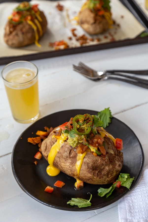 A stuffed potato on a black plate with a glass of beer and utensils, and a a platter with stuffed potatoes in the background.