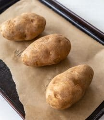 Three potatoes on a parchment lined baking sheet.