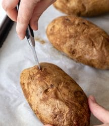 A hand slicing open the center of a baked potato.