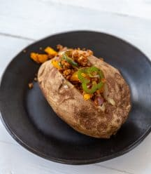 A baked potato on a black plate with a meaty filling stuffed in the center.