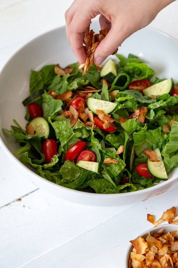 A hand sprinkling coconut bacon over a large salad in a white bowl with a bowl of coconut bacon next to it.