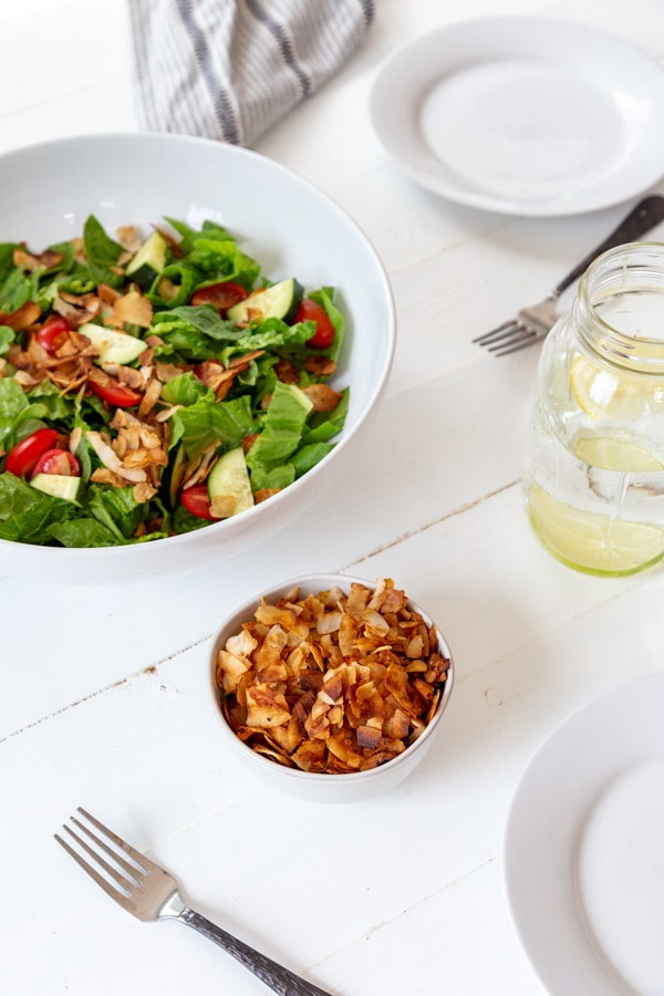 A large white bowl of salad with two white plates, forks, a glass of white wine, and a white bowl of coconut bacon on a white wood table.