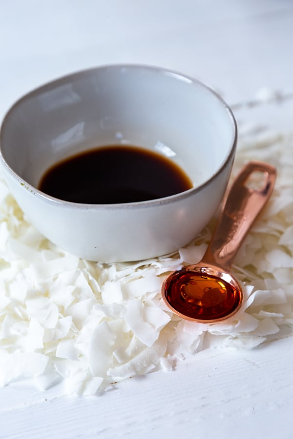 A white bowl with liquid smoke and coconut flakes and a copper spoon with maple syrup on a white table.