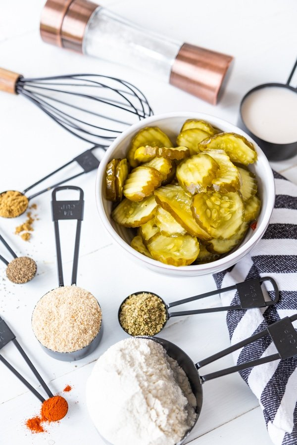A bowl of pickle chips and black measuring spoons with flour and spices on a blue and white striped towel.