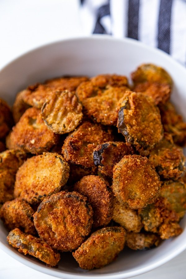 A close up shot of fried pickles in a white bowl with a striped towel next to the bowl.
