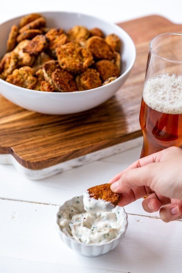 A hand dipping a fried pickle into ranch dressing with a bowl of fried pickles and a glass of beer in the background.