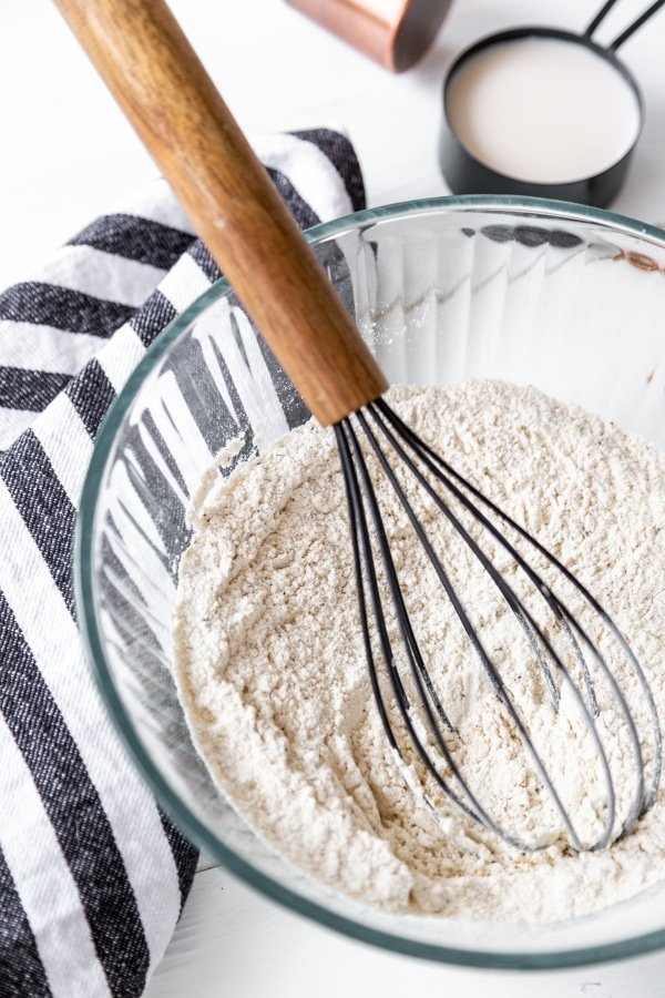 A glass bowl with flour and spices and a wooden whisk in the bowl.