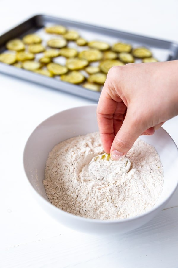 A hand dipping a pickle chip into a bowl of flour with a pan of pickle chips in the background