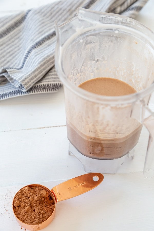 A pitcher of chocolate milk with a gold measuring cup with cocoa powder and a towel n the background.