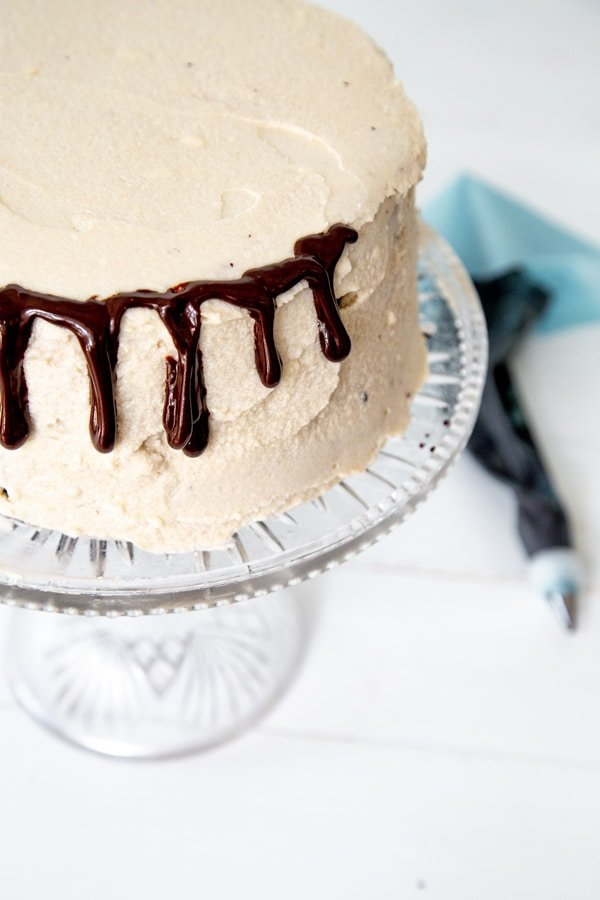 A cake frosted with vanilla icing with drips of chocolate ganache down the sides and a blue pastry bag next to it.