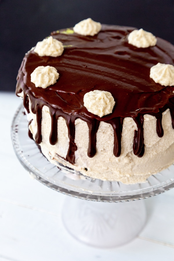 A cake with vanilla frosting and chocolate ganache on the top and dripping down the sides with dollops of frosting around the edge of the cake.