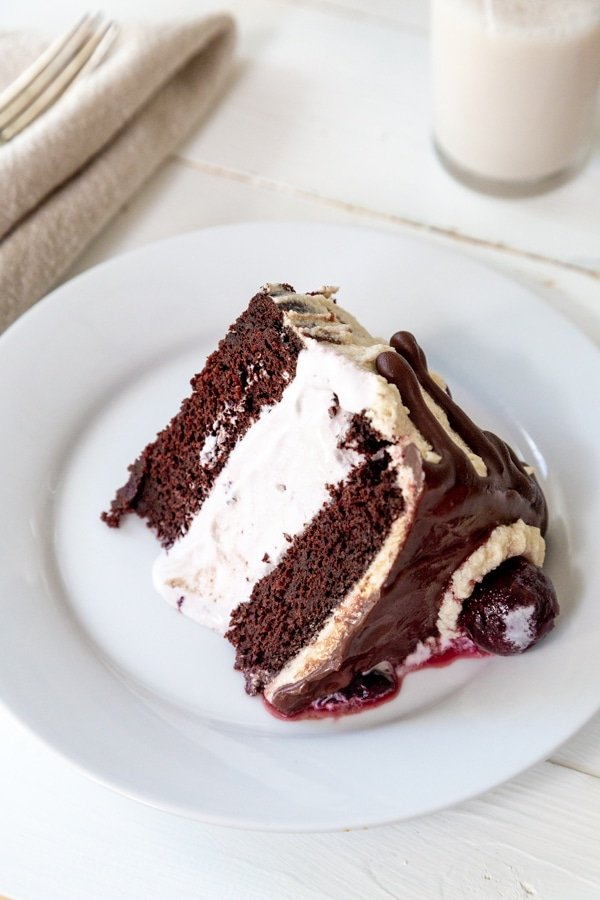 A slice of chocolate and cherry ice cream cake on a white plate with a glass of milk in the background.