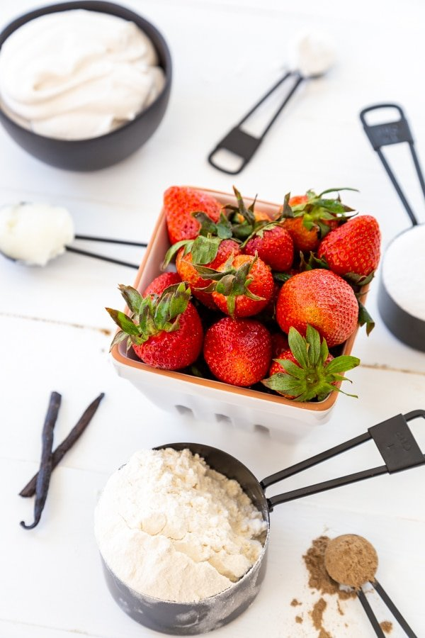 A white container of strawberries and black measuring cups and spoons with flour, sugar and spices.