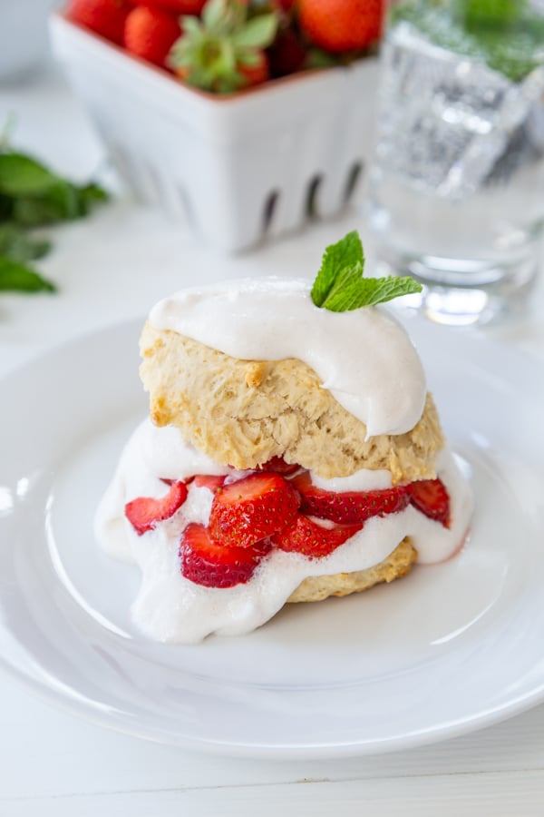 Strawberry shortcake on a white plate on a white wood table with a white carton of strawberries in the background.