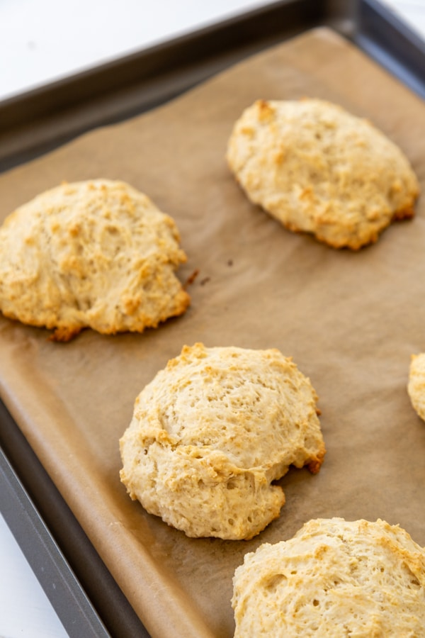 A parchment lined baking sheet with shortcake biscuits.