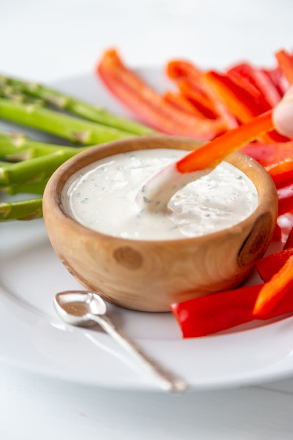 A hand dipping a slice of red pepper into a wood bowl of ranch dressing.