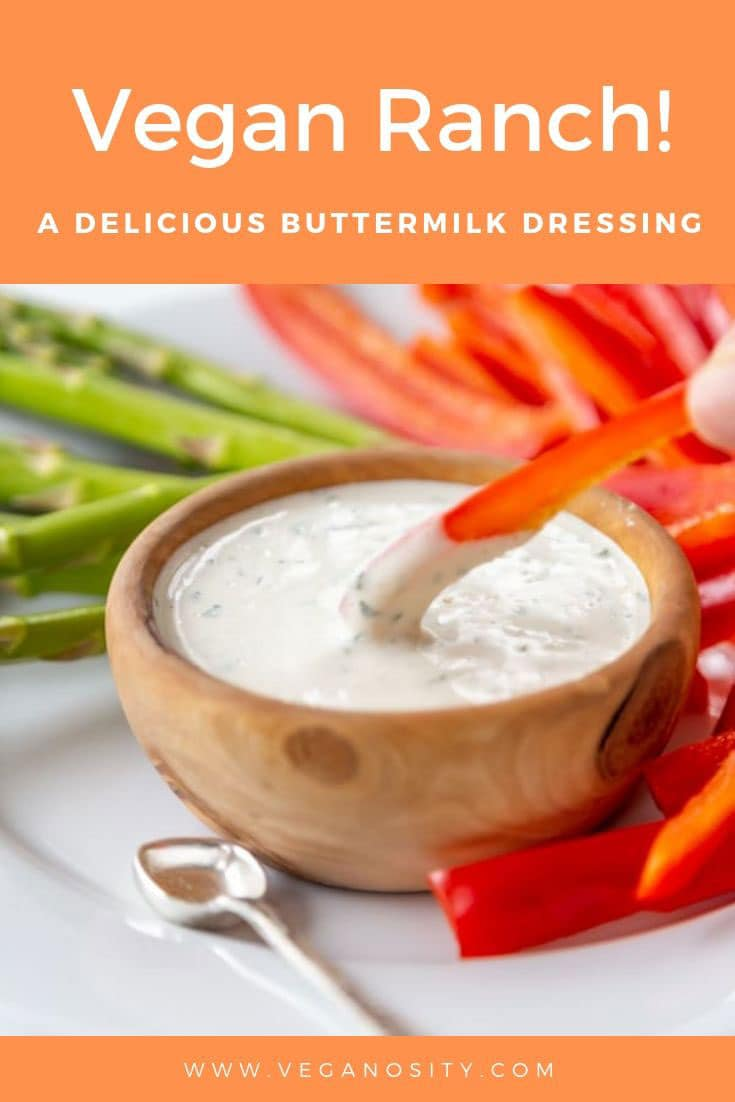 A Pinterest pin with orange background for vegan ranch dressing with a picture of a wood bowl of ranch and a hand dipping a slice of bell pepper in the dip.