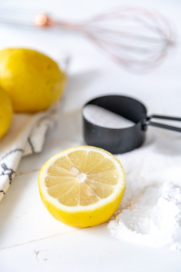 Lemons, flour, and sugar in a black measuring cup on a white wood board.