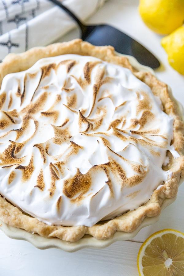 A whole lemon meringue pie with a black pie serving knife and lemons around it.
