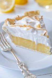 A slice of lemon meringue pie on a white plate with a silver fork resting on the plate.