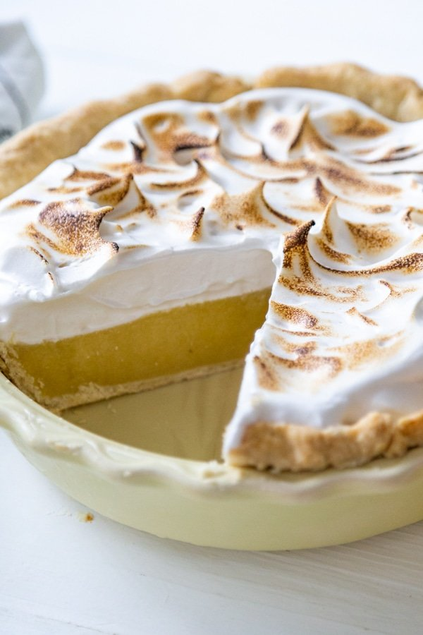 A lemon meringue pie in a yellow pie plate with a slice missing.
