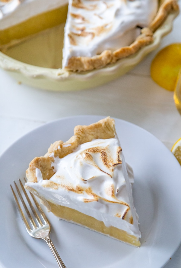 A slice of lemon meringue pie on a white plate with a silver fork and the whole pie behind it.