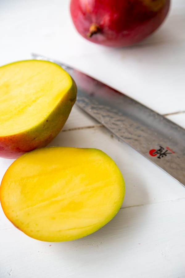 A mango sliced in half with a knife on a white table.