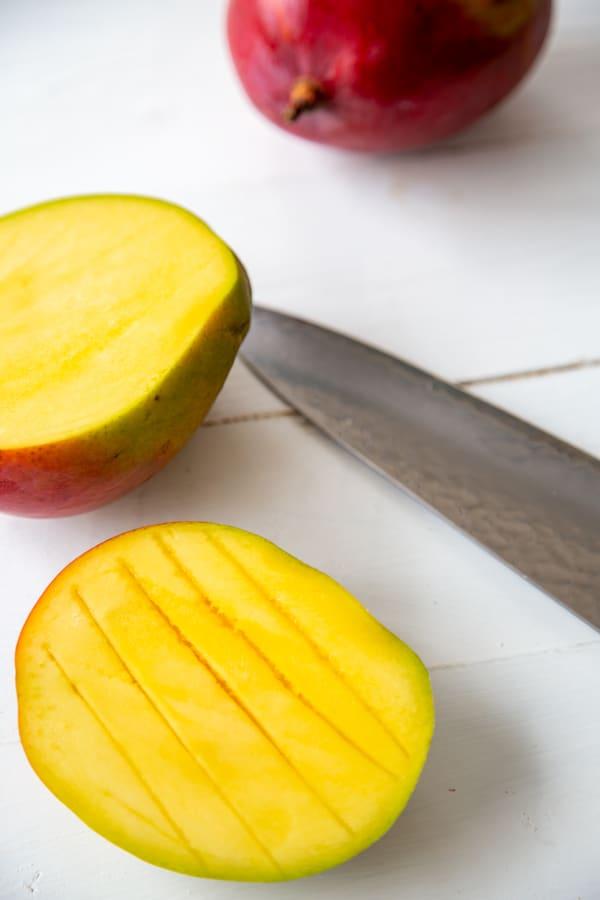 A mango cut in half with one half sliced vertically.