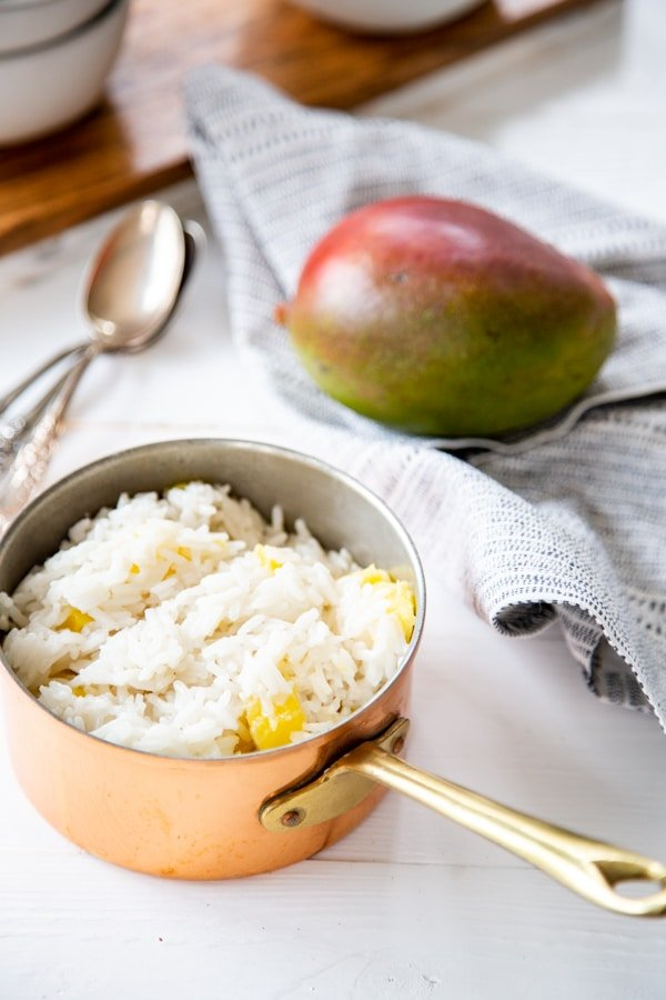 A copper pot with rice and a mango and spoon next to it.