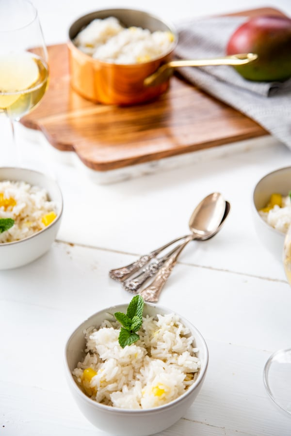 A tablescape with white bowls with mango rice and a copper pot of rice.