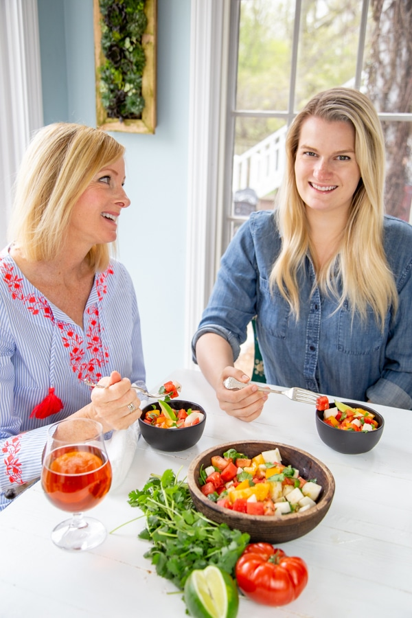Two blonde women smiling and eating salads at a white table.