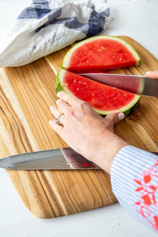 A woman's hand holding half of a watermelon and slicing it in the center with a knife.