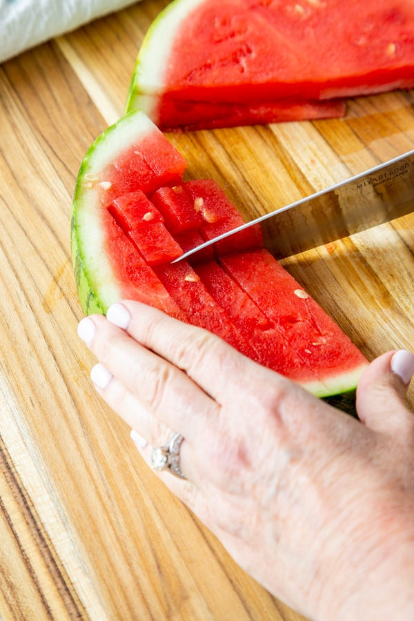 A hand with a sharp knife cubing a watermelon.