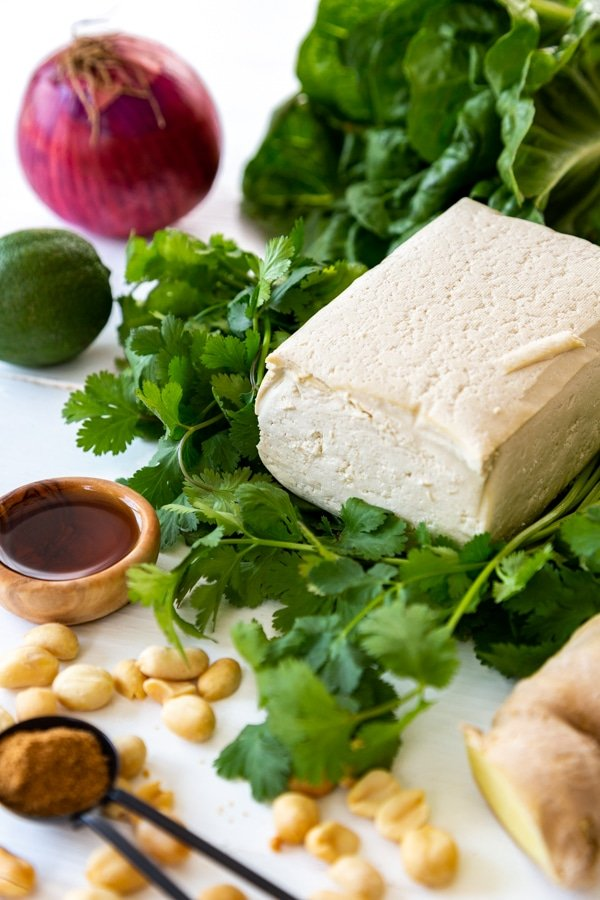 Ingredients for lettuce wraps, a block of tofu, lettuce, peanuts, herbs and spices.
