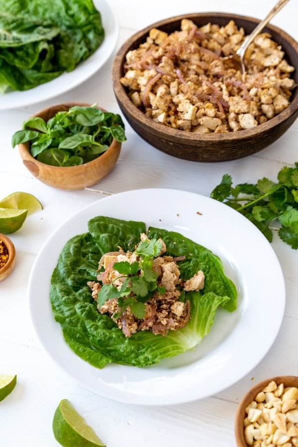 A lettuce leaf on a white plate with tofu veggies and basil leaves on top.
