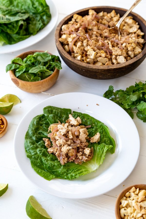 A lettuce leaf on a white plate with a pile of vegetable tofu on top.