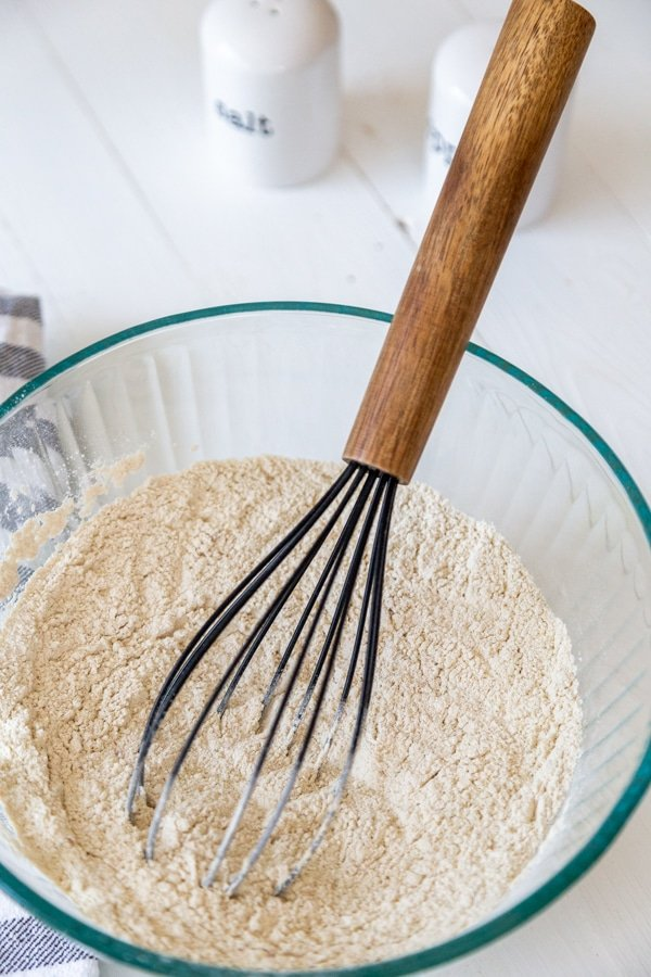 A glass bowl with flour and a wooden whisk.