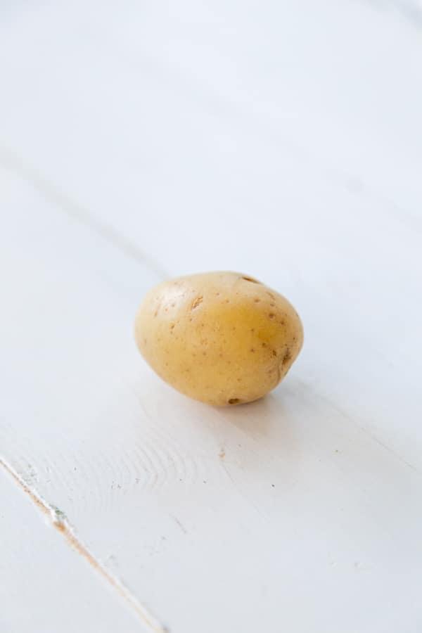 A small potato on a white wood table.